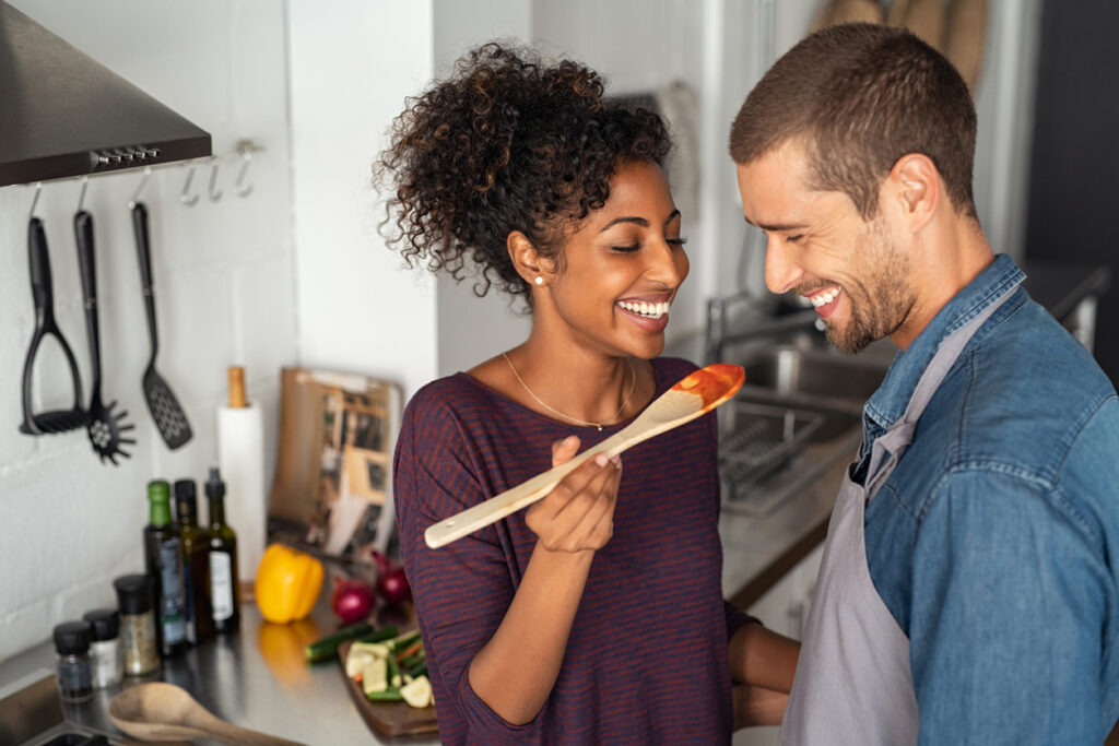 Young couple tasting tomato sauce while cooking in the kitchen. Cheerful man and smiling woman holding spatula in hand ready to taste red sauce. Multiethnic couple cooking together at home.
